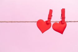 Two red hearts are hung on clips with place for text on a pink background. Valentine's day holidays and anniversary concept.