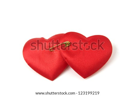 Two red hearts bound together with golden safety pin isolated on white background