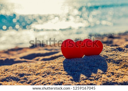 Two red hearts in the sand on the sea background. Valentine's day postcard.