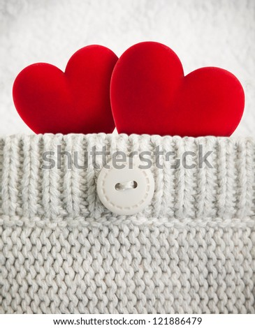 Two red hearts in wool pocket - stock photo