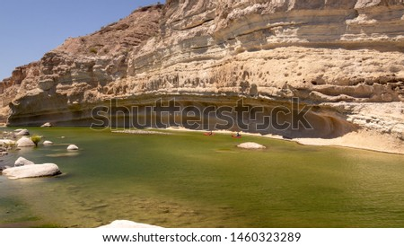 two red kayaks kayaking in a green river with limestone cliffs