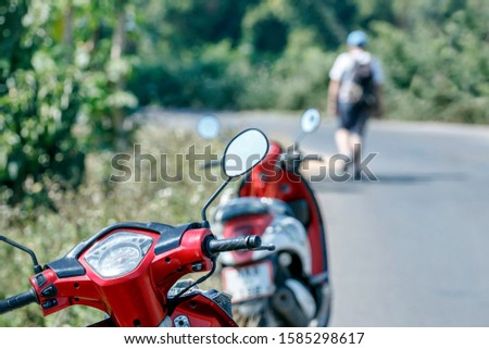 Two red motorcycles are standing on the side of a rural road, a man is walking on a blurred background.