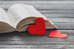 two red paper hearts and open book on wooden table