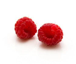 Two red raspberries isolated on white background