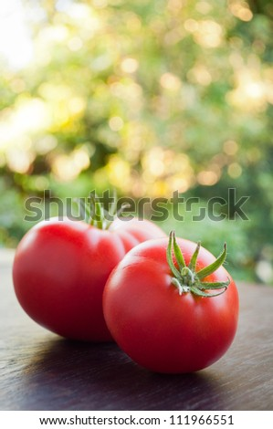 Two red tomatoes on a wooden table.