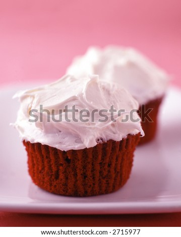 Two red velvet cupcakes with vanilla frosting