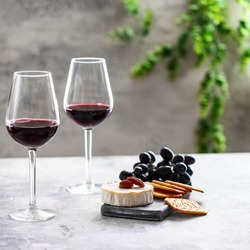 Two red wine glasses and cutting board with dgrapes,cheese and crackers on restaurant table. Wine lover concept