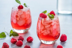 Two refreshing red translucent drinks with ice and raspberries. The raspberry juice is garnished with a green leaf, and there are pieces of ice and raspberries scattered around the drinks.
