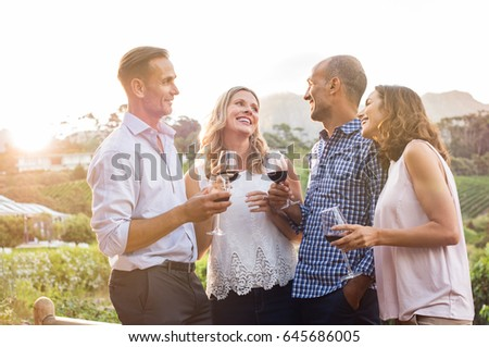 Two relaxed mature couples laughing and enjoy glasses of red wine at sunset. Group of happy friends celebrating outdoor and toasting with glassess. Happy man and smiling women having fun at vineyard.