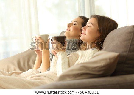 Two relaxed roommates in winter sitting on a sofa in the living room of a house interior