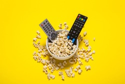Two remotes from the TV, TV tuner lie in a bowl with popcorn on a yellow background. Concept series, film, sports. Banner. Flat lay, top view