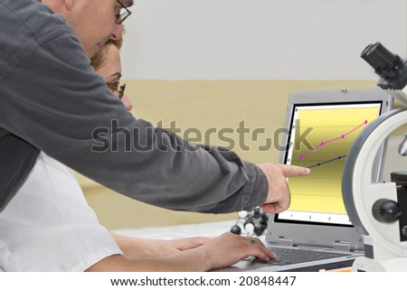 Two researcher colleagues analyzing the graph of the experiment results on a laptop-close-up.