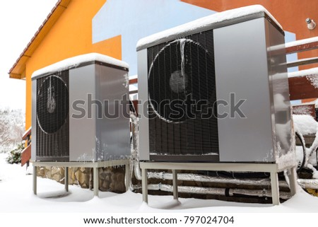 Two residential modern heat pumps buried in snow #797024704