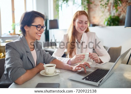 Two restful businesswomen looking through online shops assortment while having coffee in cafe