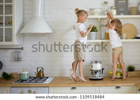 Two restless fidgety children wearing casual clothes standing barefooted on kitchen counter, searching for hidden sweets. Cute blonde little boy playing at home with his adorable baby sister stock photo
