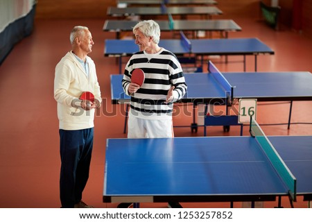 Two retired sportsmen in casualwear standing by tennis table while discussing some moments