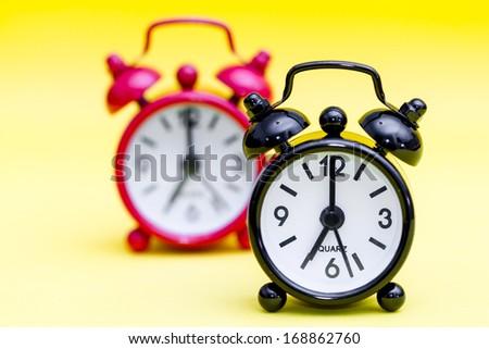 Two retro alarm clocks on yellow background displaying seven o\'clock.