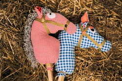 Two retro cotton fabric horse toy on a stick lying on the hay. Vintage rustic background.