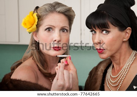 Two retro-styled Caucasian women in mink coats smoke weed