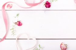 Two ribbon magic pink hearts on white wooden backround, roses and petals. Valentine day concept