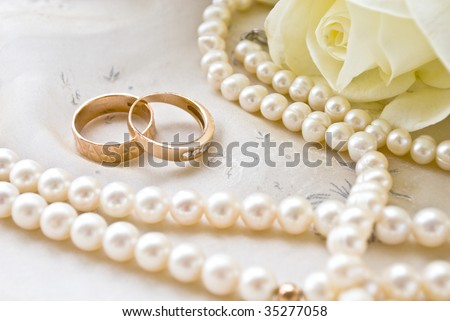 two rings and pearls and white roses