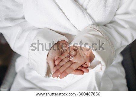 two rings in the hands of the bride