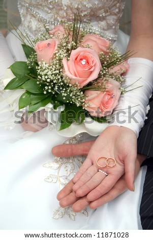 Two rings on palms of a newly-married couple, a bouquet of roses in a hand
