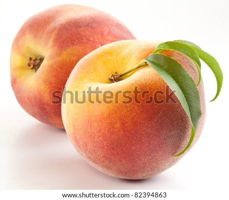 Two ripe peach with leaves on white background.