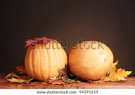 two ripe pumpkins and autumn leaves on wooden table on brown background