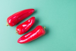 Two ripe red bell peppers on a bright yellow background. Concept healthy eating. Copy space