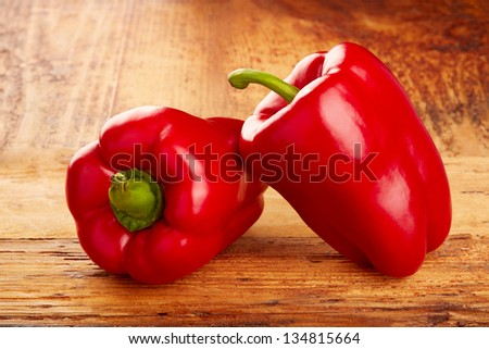 Two ripe red peppers on table