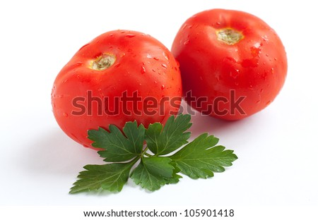 Two ripe red tomatoes and parsley leaves. Drops of water on tomato