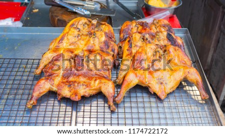 Two roasted chicken lay on the grill. - Shutterstock ID 1174722172