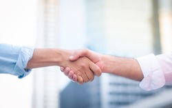 Two roll up shirt sleeves businessman shaking hands agreement with blurred building background, successful business collaboration and teamwork,Team agreement in hands gesture communication
