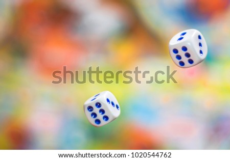 two Rolling dice on blurred colorful background. bone to game. Board games, gaming moments in dynamics. concept of luck, winning, victory #1020544762