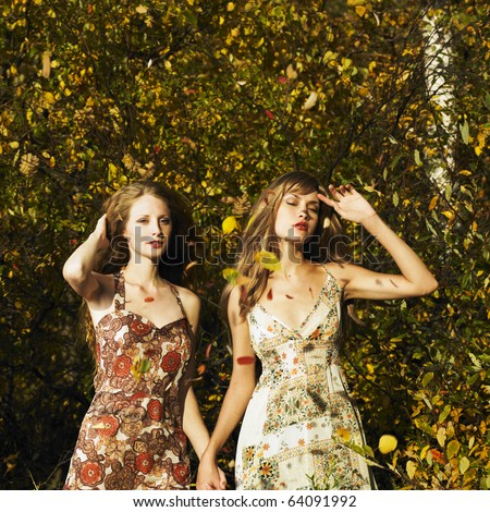 Two romantic girl surrounded by autumn leaves