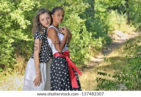 Two romantic girl surrounded by leaves in forest