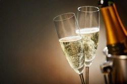Two romantic glasses of sparkling champagne alongside a bottle in an ice bucket and copy space to celebrate a wedding, anniversary, New Year or Valentines day