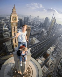 Two roofers do selfie on tall skyscraper in Dubai, United Arab Emirates