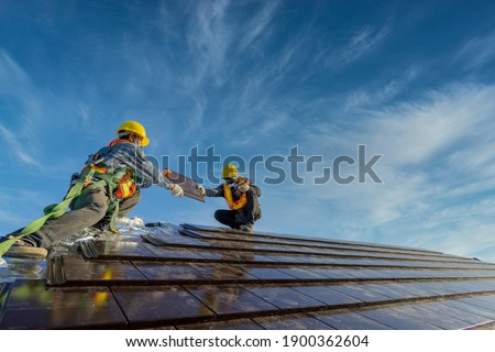 Two roofers Wearing safety clothing is working as a team to install the roof of the house that Ceramic tile roof at construction site