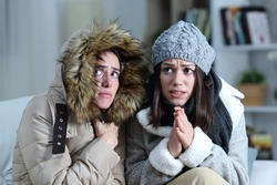 Two roommates shivering in a cold winter day on a couch in the living room at home
