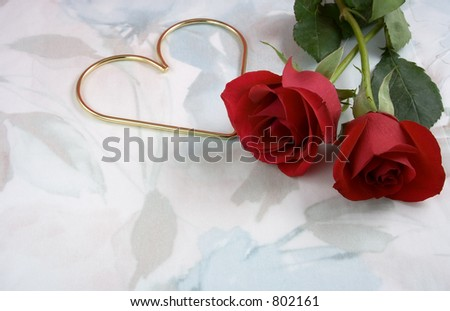 Two roses and a gold metal heart on a very soft, flowery background. - stock photo