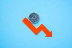 two rouble coin on blue background with red arrow down. exchange rate chart. ruble depreciation. Exchange rate of rouble fall. Rouble to dollar