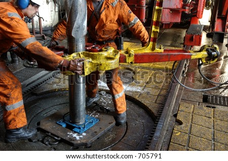 Two roughnecks breaking a connection with help from tongs. Offshore oil rig.