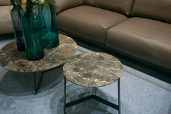 Two round stone tea tables  with three blue glass vases standing near brown leather sofa - photo with selective focus