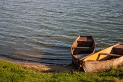 Two rowboats are moored to the shore. Metal boats are attached to the shore with steel chains. Chains guard boats on a summer day.
