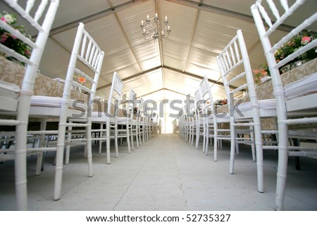 Two rows of chairs at a wedding reception in a massive tent