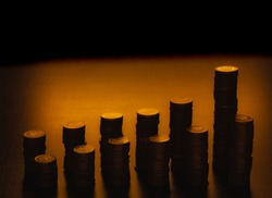 Two rows of coin stacks. Ascending trends. Silhouettes of coin stacks isolated on dark background. Stacks of various heights. Two parallel vertical bar chart.