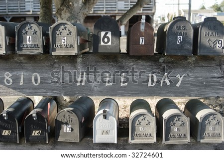 Two rows of U.S. mailboxes sitting on a fence.