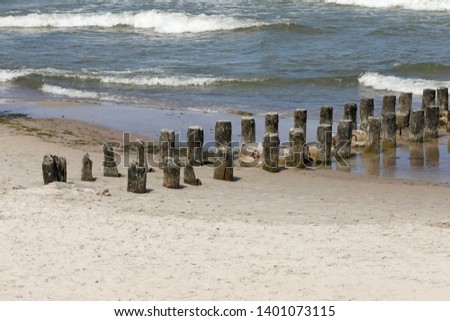 Two rows of wooden breakwaters. These wooden breakwaters serve to protect the coast against the sinister effects of destructive sea waves in Kolobrzeg in Poland #1401073115